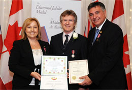 MP Stella Ambler MP and MPP Charles Sousa MPP present Queen's Diamond Jubilee medal to guitarist Rik Emmett. photo by Rob Beintema